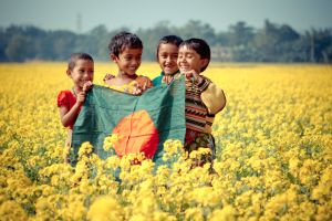 Bangladeshi children playing in a field of mustard shrubs.